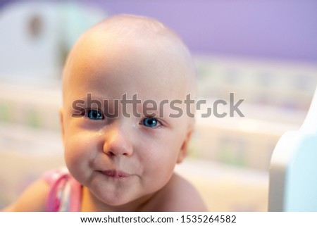 The baby is upset, crying. Girl crying while standing in her crib. Face close up. Illness, violence, emotions. #1535264582