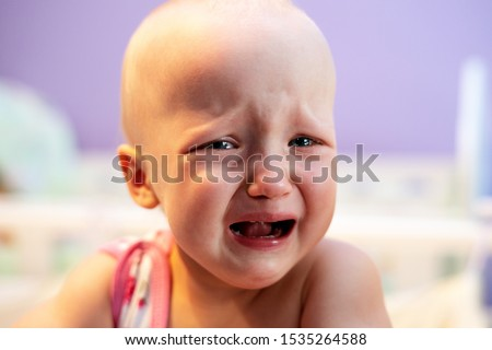 The baby is upset, crying. Girl crying while standing in her crib. Face close up. Illness, violence, emotions. #1535264588