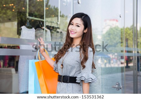 young woman carrying shopping bags and smiling in mall #153531362