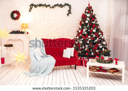 Decorated Christmas interior with red sofa, white walls and big Christmas tree.  #1535325203