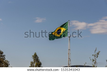 Image of brazil flag in clear day and blue horizon hoisted on metal flagpole. Small clouds in the sky at the bottom of the flag appear scattered. National symbol of Brasile. Brazilian flag #1535341043