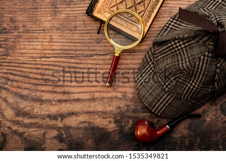 Literary fiction, investigate crime and mystery story conceptual idea with sherlock holmes detective hat, smoking pipe, retro magnifying glass and old book isolated on wood table top with copy space #1535349821