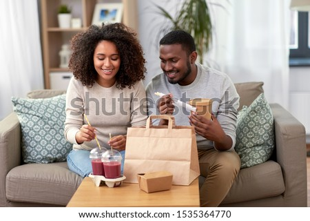 eating and people concept - happy african american couple with takeaway food and drinks at home #1535364770