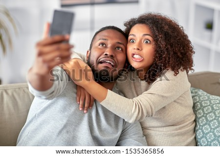 family, technology and people concept - african american couple with smartphone taking selfie and making funny faces at home