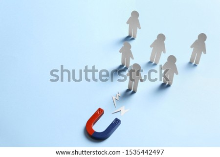 Magnet attracting paper people on light blue background, space for text. Business rivalry concept #1535442497