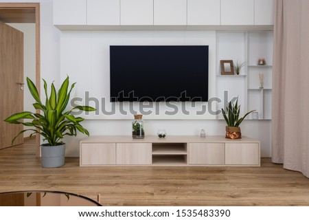 Interior of contemporary living room with TV on the wall #1535483390
