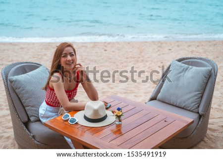 traveler girl in red dress sit on the chair in beach with vacation trip in emotional relax and smile for relax concept #1535491919