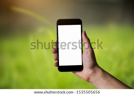 Hand holding white mobile phone with blank white screen in green nature background. #1535505656