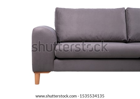 Patterned cushions on sofa next to wooden table and plant in dark apartment interior. White background. Real photo #1535534135