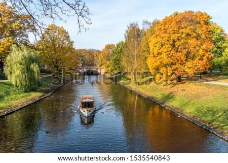 River Running through the Center of a City in Northern Europe in Autumn with a Tour Boat