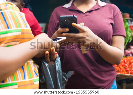 Satisfied Young African hipster girl, types text message on cell phone, enjoys online communication, types feedback, Doing online Transaction, In Local Market , technology concept #1535555960