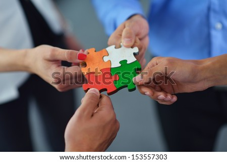 Group of business people assembling jigsaw puzzle and represent team support and help concept #153557303