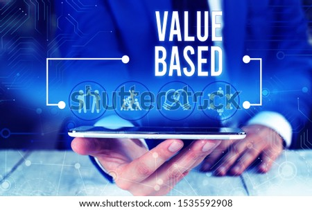 Word writing text Value Based. Business concept for Considering the product worth in satisfying the customer Male human wear formal work suit presenting presentation using smart device. #1535592908