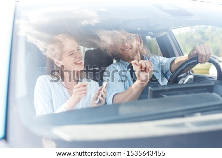 Happy young adult woman and cheerful man ride in car together, listening good music, dancing, having fun and smiling wide. Two friends travelling on weekend #1535643455