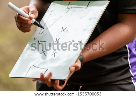 Close up of Female sport coach hand writing game plan on small whiteboard in the field before the game #1535700053