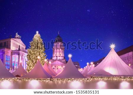 Iluminated Christmas market Gandarmenmarkt in Berlin, Germany, at night with stars shining on illuminated Concert House, church, white canvas tents and giant Xmas tree #1535835131