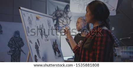 Medium shot of female designers discussing video game artwork