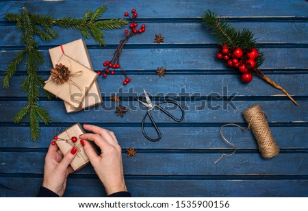 Woman decorating Christmas gifts. Presents wrapping inspirations. Hands, gift boxes, ball of jute, cone, anise, fer tree branches  and retro scissors on blue rustic wooden background. New Year  #1535900156