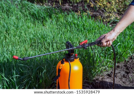 The woman's hand holds the handle of an orange sprayer, from which jets of an chemical solution gush against the background of a green bed. The concept of marriage level of cheap garden equipment. #1535928479