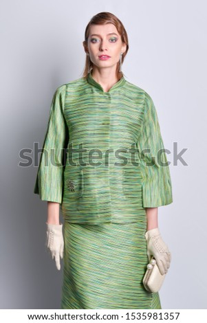 Beautiful fashion model in silk green jacket and skirt with old fashioned hairstyle #1535981357