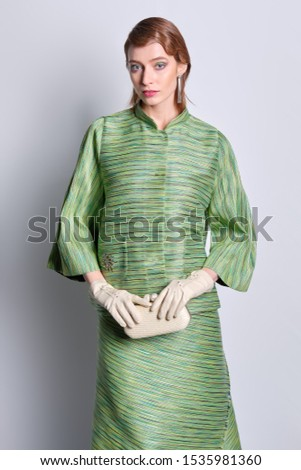 Beautiful fashion model in silk green jacket and skirt with old fashioned hairstyle #1535981360
