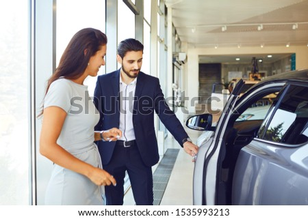 A young woman buys a new car in an auto salon #1535993213