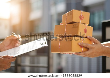 Delivery man holding parcel boxes while a man is signing documents in morning background #1536058829