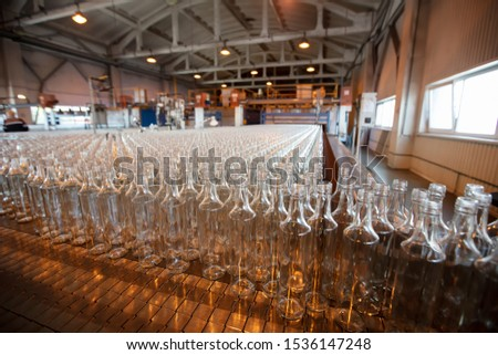Glassworks. Glass industry. Many glass bottles on a factory conveyor. #1536147248