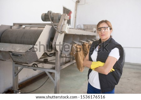 Woman posing near to machine conveyer belt for olives packaging industry #1536176516
