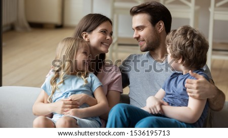 Happy parents with little daughter and son sitting on couch, looking at each other, enjoying tender moment together, children sitting on smiling mum and dad lap, cuddling, expressing love and unity #1536195713