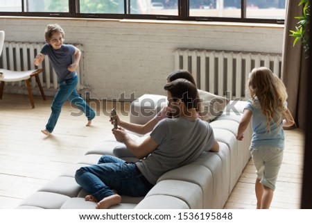 Children playing tag and touch, running while mother and father relaxing on couch, little daughter and son having fun in living room together, mum and dad using smartphone apps, chatting online #1536195848