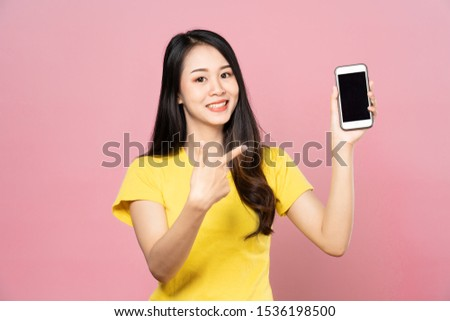 Portrait of Asian beautiful young woman holding smartphone and pointing finger on mobile phone with smile face. The girl standing and looking at camera in studio. Advertisement & presentation concept. #1536198500
