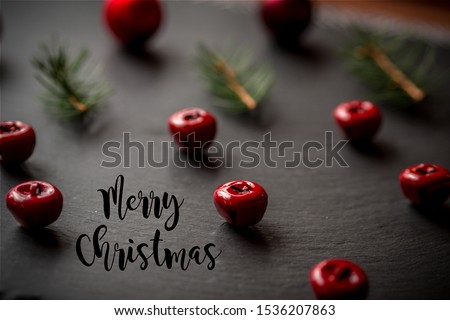 closeup of Christmas decorations, jingle bells, fir and pinnacles on black textured background forming a regular and repetitious pattern