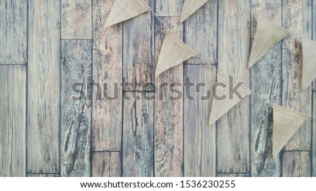 Flags from canvas on a thread. Garland on a wooden wall background #1536230255