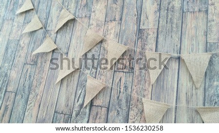 Flags from canvas on a thread. Garland on a wooden wall background #1536230258