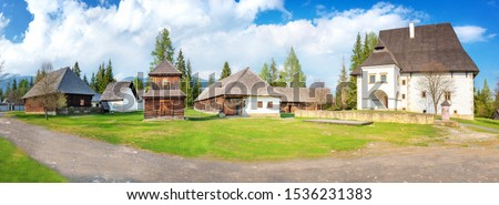 Old traditional houses and belfry of village Pribylina in Liptov region (SLOVAKIA) - PANORAMA #1536231383