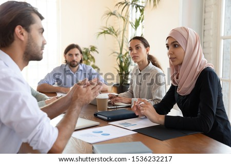 Serious caucasian businessman talking to multicultural business people at meeting table, male manager negotiator mentor teaching diverse team work group consulting clients at conference briefing Royalty-Free Stock Photo #1536232217