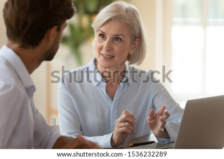 Middle aged old businesswoman manager mentor speaking to businessman client offering insurance banking services deal teaching intern or convincing customer at business office meeting sit at table. #1536232289