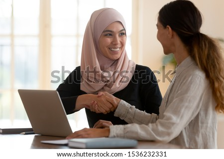 Happy asian muslim businesswoman sales manager shake hand of caucasian lady client make deal with female customer at meeting with laptop, diverse women partnership, respect and collaboration concept Royalty-Free Stock Photo #1536232331