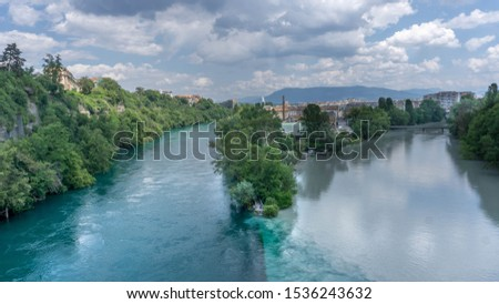 Dark and light river merge into a single one. View from above. White shallow clouds on a blue sky. The concept of the unity of opposites.  The river on the left is the Rhone, which has just left Lake