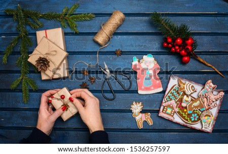 Woman decorating Christmas gifts. Presents wrapping inspirations. Hands, Russian traditional gingerbread cookies, gift boxes, ball of jute, cone, anise, fer tree branches  and retro scissors on blue  #1536257597