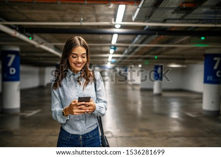 Businesswoman in underground garage. Elegant woman using smartphone in parking garage. Fashionable young woman texting on smartphone. Businesswoman in a parking garage #1536281699