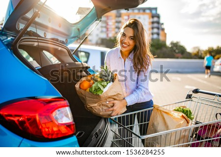 Happy woman walking to the car after shopping at the supermarket. Pretty Adult Woman Holding Groceries at Car. Busy woman after shopping in the supermarket #1536284255