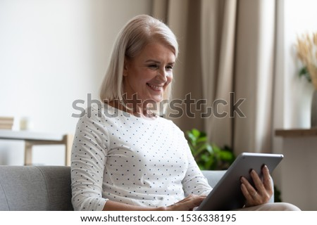 Smiling mature old woman holding using digital tablet relaxing sit on sofa reading e book in reader app, happy middle aged senior grandma browsing internet shopping online on pad computer at home #1536338195