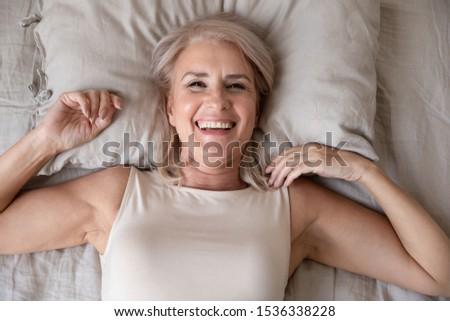Happy fresh beautiful mature older woman awake after healthy sleep stretch wake up in cozy comfortable bed, smiling middle aged lady enjoy good morning looking at camera, close up portrait, top view
