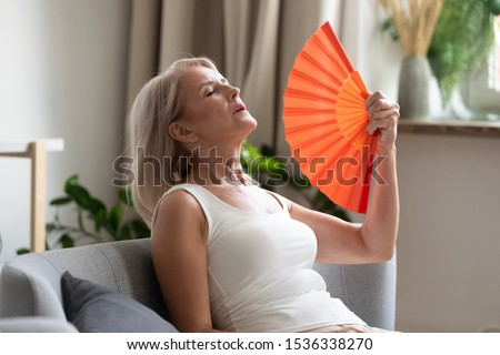 Stressed annoyed old senior woman using waving fan suffer from overheating, summer heat health hormone problem, no air conditioner at home sit on sofa feel exhaustion dehydration heatstroke concept #1536338270