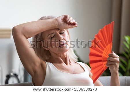 Tired overheated middle aged lady wave fan suffer from menopause exhaustion complain on heat at home, stressed old woman sweat feel uncomfortable hot in summer weather problem without air conditioner #1536338273