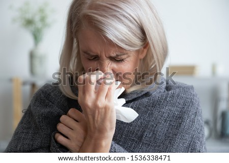 Ill mature woman covered with blanket blowing running nose sneeze in tissue suffer from allergy flu, allergic old lady hold handkerchief got hay fever rhinitis symptom cough at home, allergy concept #1536338471
