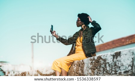 Charming elegant African female hipster is taking a selfie while sitting on a stone wall outdoors; stylish black girl in yellow overalls and a denim jacket is taking pics on her cell phone on a street