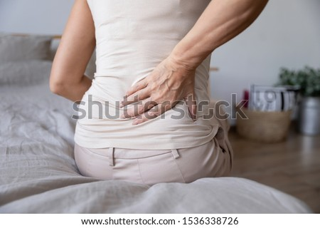 Old mature woman sit on bed touch back feel morning backpain suffer from lower lumbar discomfort muscle pain wake up with backache after sleep on uncomfortable mattress concept, close up rear view #1536338726